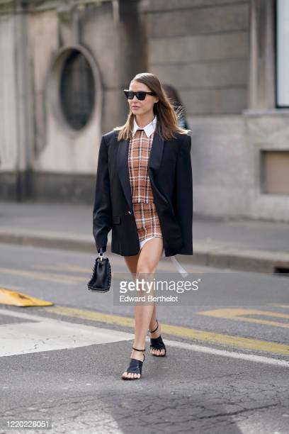 Sophia Roe wears sunglasses, an oversized black blazer jacket, a brown checked top and short skirt, a white shirt, a black bag, black leather shoes,...