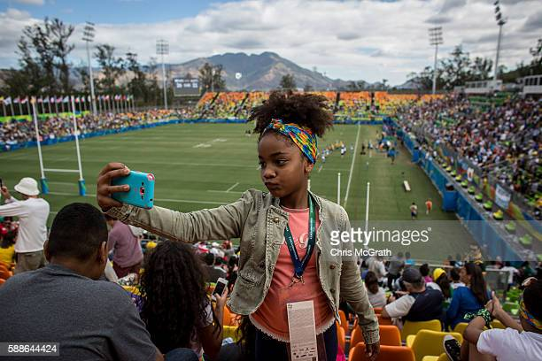 Sophia Rotha from the Cantagalo 'favela' community takes a selfie in front of the Olympic Rugby 7's action on August 11 2016 in Rio de Janeiro Brazil...