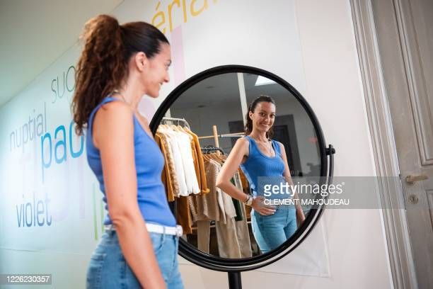 Sophia Torres store manager for the Sugar clothes brand poses with a Sugar manufactured blue top in the company show room in Marseille south of...