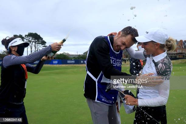 SophiaPopov of Germany celebrates victory with caddie Maximilian Mehles on the 18th green as they are showered with champagne during Day Four of the...