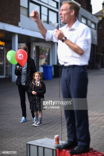 Sophie Black aged six holds balloons while Jim Murphy Shadow Secretary of State for International Development talks to members of the public in...