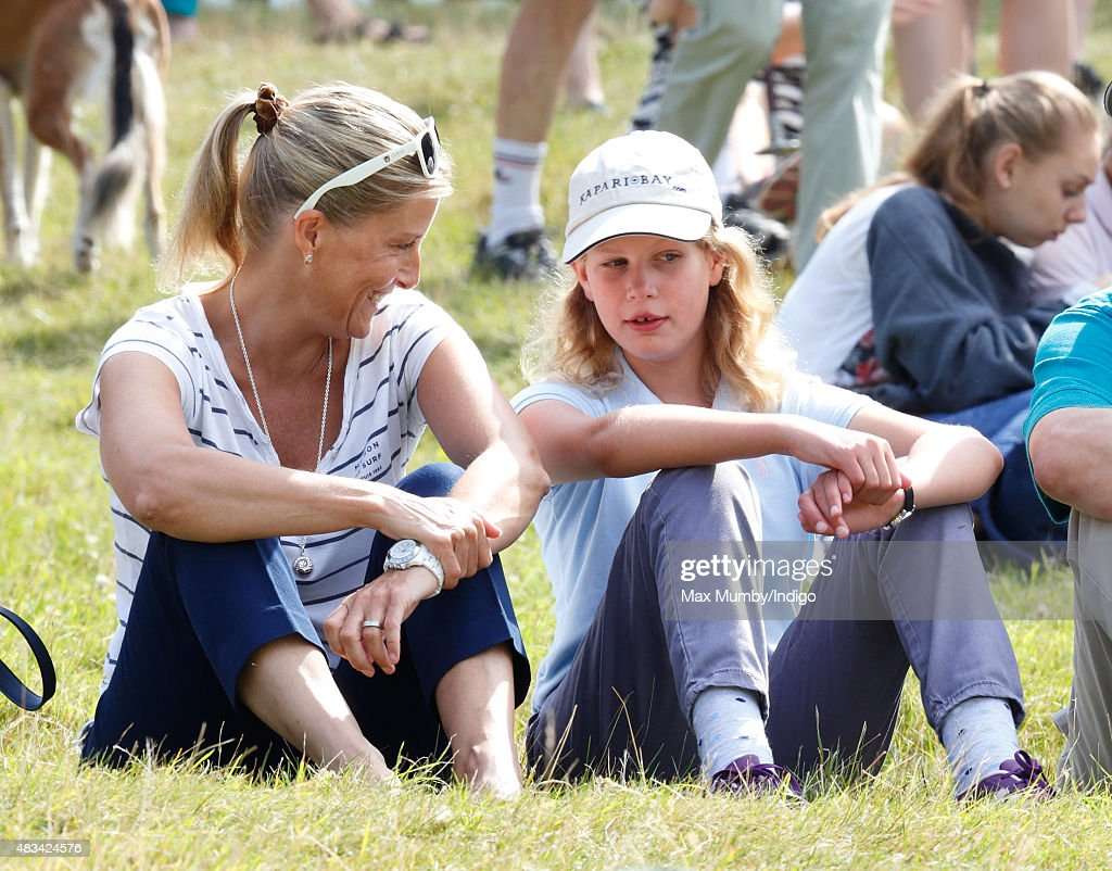 Sophie, Countess of Wessex and daughter Lady Louise Windsor sit on the grass to watch the cross country phase of the competition as they attend day 2 of the Festival of British Eventing at Gatcombe Park on August 8, 2015 in Stroud, England.