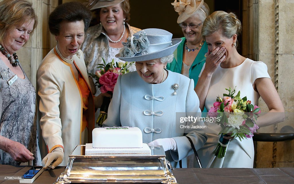 Sophie, Countess of Wessex and Princess Anne, Princess Royal look on as Queen Elizabeth II cuts a Women's Institute Celebrating 100 Years cake at the Centenary Annual Meeting of The National Federation Of Women's Institute at the Royal Albert Hall on June 4, 2015 in London, England.