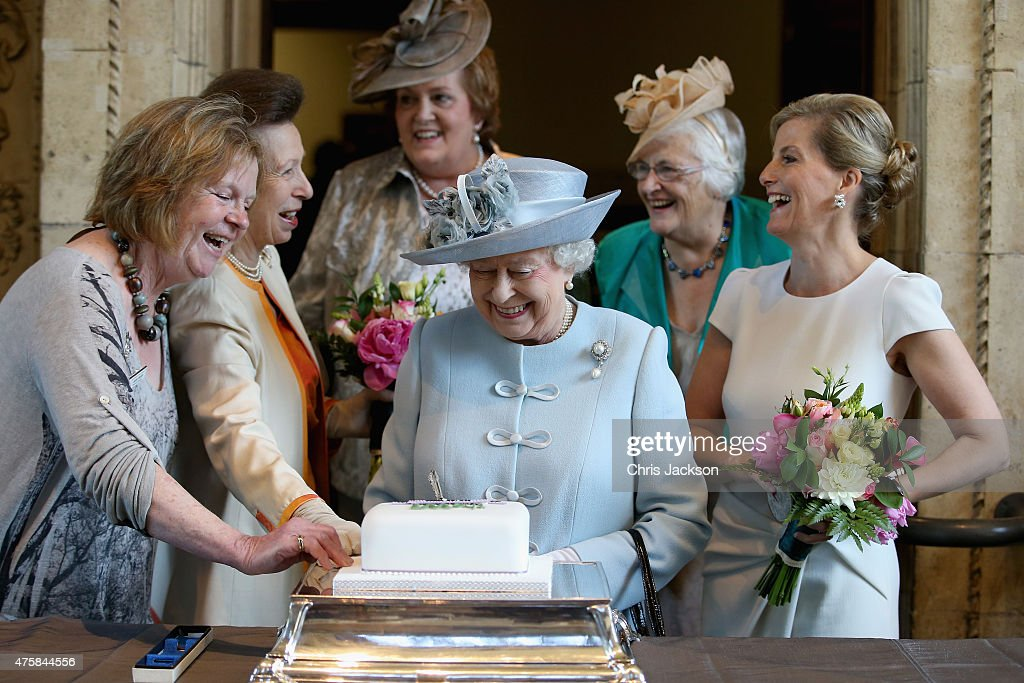Sophie, Countess of Wessex and Princess Anne, Princess Royal look on as Queen Elizabeth II cuts a Women's Institute Celebrating 100 Years cake at the Centenary Annual Meeting of The National Federation Of Women's Institute at Royal Albert Hall at the Royal Albert Hall on June 4, 2015 in London, England.