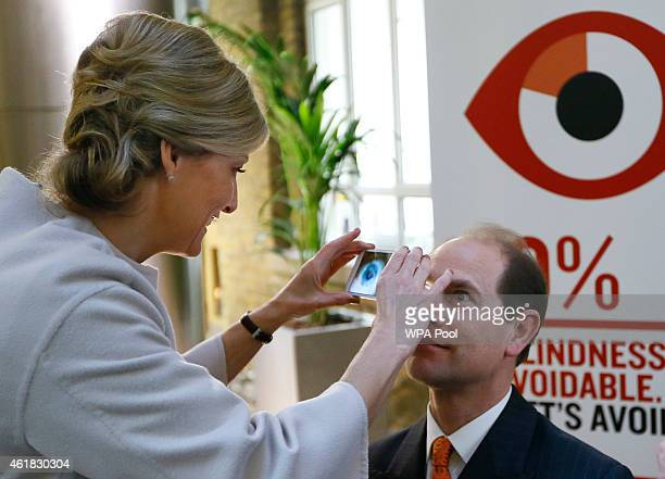 Sophie Countess of Wessex examines the eye of Prince Edward Earl of Wessex using a Portable Eye Examination Kit which turns a smart phone into a...