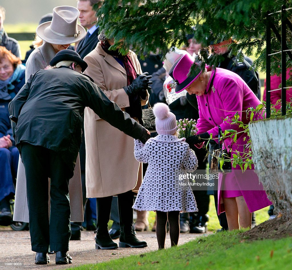 Sophie, Countess of Wessex (L) looks on as a policewoman escorts a young girl to present Queen Elizabeth II (R) with a bunch of flowers as she leaves St. Mary Magdalene Church, Sandringham after attending Sunday service on December 30, 2012 near King's Lynn, England.