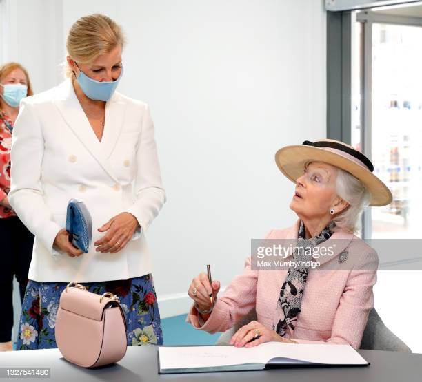 Sophie, Countess of Wessex looks on as Princess Alexandra signs the visitor's book during a visit to the Guide Dogs for the Blind Association to open...