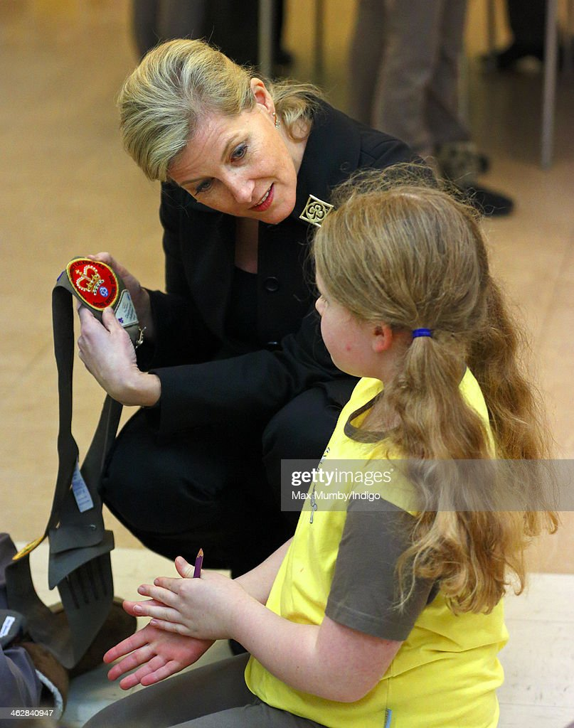 Sophie, Countess of Wessex, President of Girlguiding, looks at a Royal Wedding sash badge as she helps out with Brownies activities during a visit to 5th Frimley Brownies on January 15, 2014 in Frimley, England.