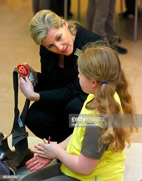Sophie Countess of Wessex President of Girlguiding looks at a Royal Wedding sash badge as she helps out with Brownies activities during a visit to...