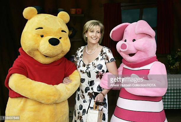 Sophie Countess of Wessex stands with storybook characters Winnie the Pooh and Piglet during a children's party