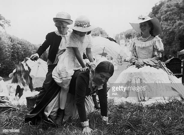 Sophie Deschamps looks amused Paprika Bommenel and Frédéric Mestre on horseback on Annie Savarin's back during the shooting of the television film...