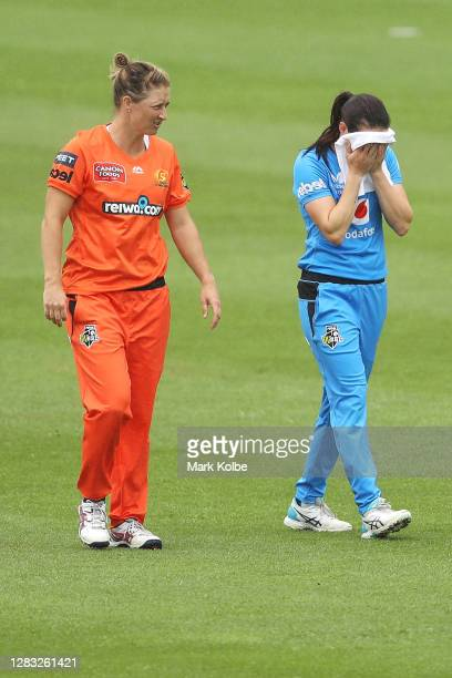 Sophie Devine of the Scorchers and Megan Schutt of the Strikers leave the field after the match was abandoned due to rain during the Women's Big Bash...