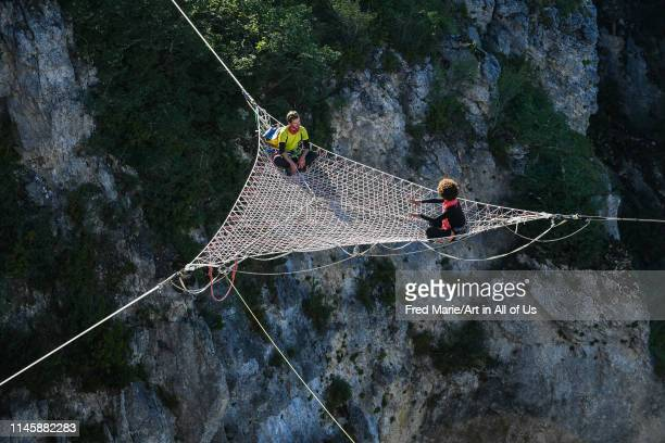 Sophie ducasse and a man in a space net on the top of a cliff, Occitanie, Florac, France on July 3, 2017 in Florac, France.