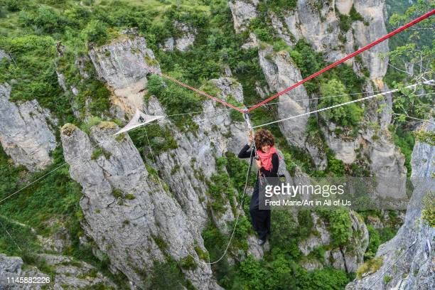 Sophie ducasse in a rope with a space net behind her on the top of a cliff, Occitanie, Florac, France on July 2, 2017 in Florac, France.