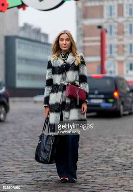 Sophie Emilie Hansen wearing a a black white stiped coat navy jogger pants red YSL bag black bag during the Copenhagen Fashion Week Autumn/Winter 17...
