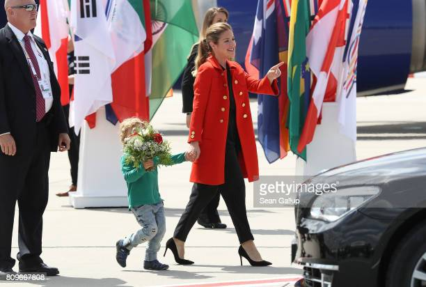 Sophie Gregoire and son Hadrien, wife and son of Canadian Prime Minister Justin Trudeau, walk to a car after the three arrived at Hamburg Airport for...