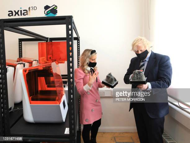 Sophie McIlveen , a Medical Visualisation Engineer at Axial 3D shows a 3D print out of a baby's heart to Britain's Prime Minister Boris Johnson...