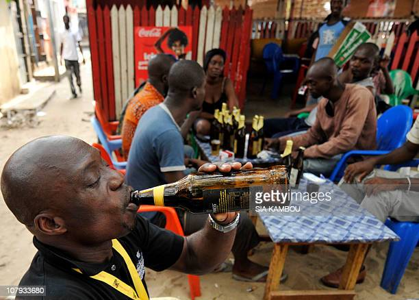 Sophie MONGALVYA man drinks a beer on January 7, 2011 at a local bar, in the Marcory quarter of Abidjan. Ivory Coast strongman Laurent Gbagbo's...