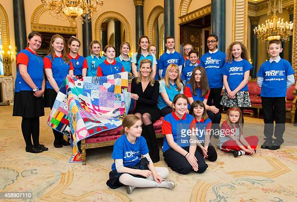 Sophie RhysJones Countess of Wessex finishes the last stitch in the 'Sew 1 Project Quilt' during a reception with Guides in the Music Room at...