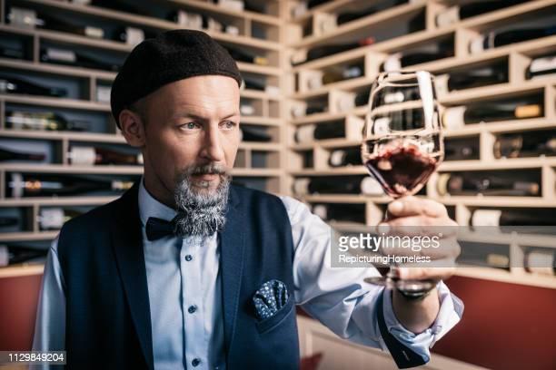 Eine sophisctated Weinverkostung, die ein Glas Wein in der Hand sorgfältig untersucht