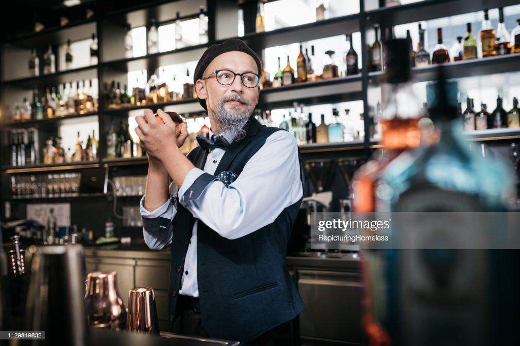 Ein ausgeklügelter Barkeeper schaut bei der Herstellung von Getränken beiseite. : Stock-Foto