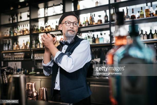 Ein ausgeklügelter Barkeeper schaut bei der Herstellung von Getränken beiseite.
