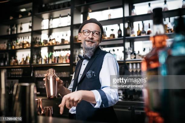 Ein raffinierter Barkeeper, der Getränke mit einem strahlenden Lächeln macht