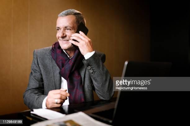 Ein anspruchsvoller Geschäftsmann im Anruf mit einem großen Lächeln