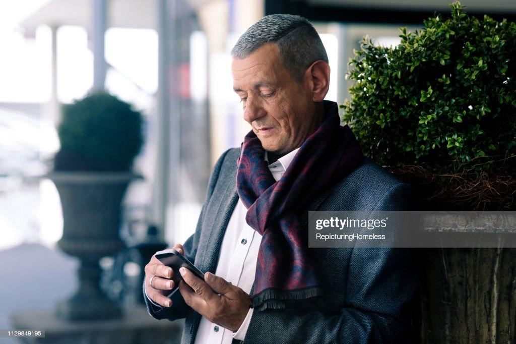 Ein ausgeklügelter Geschäftsmann schaut auf sein Handy in der Hand. : Stock-Foto