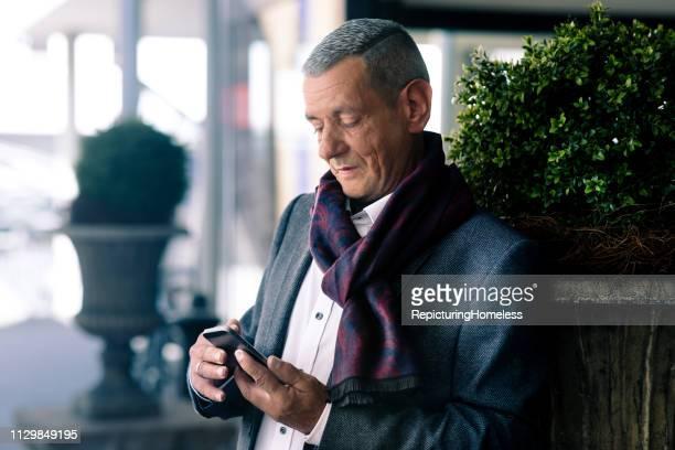 Ein ausgeklügelter Geschäftsmann schaut auf sein Handy in der Hand.