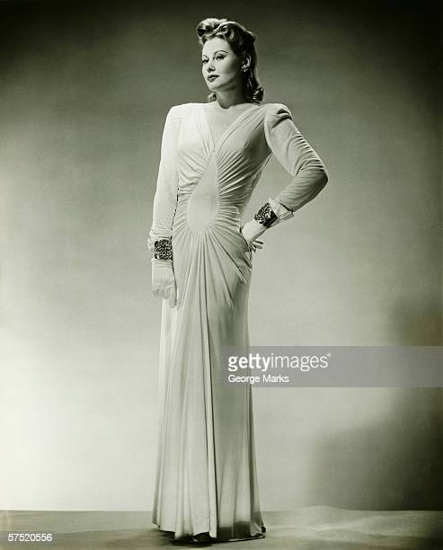 Sophisticated woman in evening gown posing in studio, (B&W), portrait