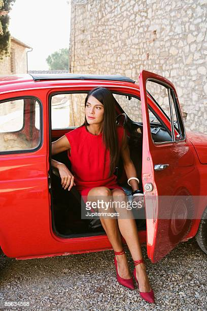 Sophisticated woman in red vintage car , Chianti , Italy