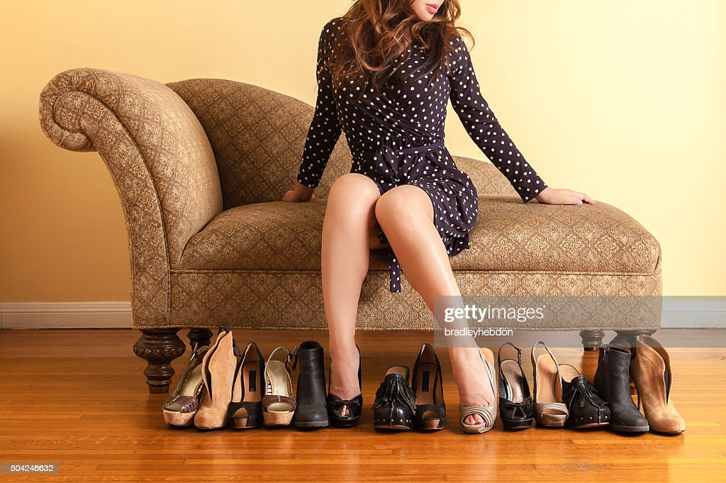 Sophisticated woman trying on shoes in store : Stock Photo