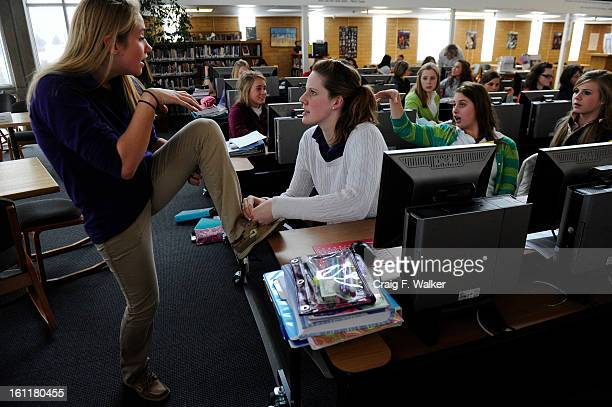 Sophomore Missy Franklin ties Katie Bell's shoe while working on a research paper for their Honors World History class in the library at Regis Jesuit...