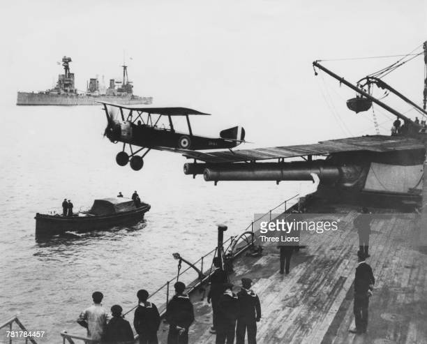 A Sopwith 1½ Strutter twoseat multirole biplane aircraft launches from a 30ft ramp mounted on the Royal Australian Navy battlecruiser HMAS...