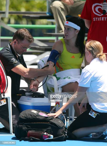 Sorana Cirstea of Romania is treated by medical staff before retiring in her first round match against Heather Watson of Great Britain during day two...