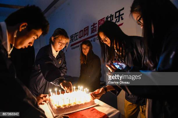 Sorana Cirstea of Romania looks at volunteers lighting candles on a birthday cake at the Volunteer Home on day five of the 2017 China Open at the...