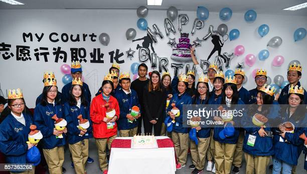 Sorana Cirstea of Romania poses for a picture with Tournament volunteers to celebrate their birthday at the Volunteer Home on day five of the 2017...