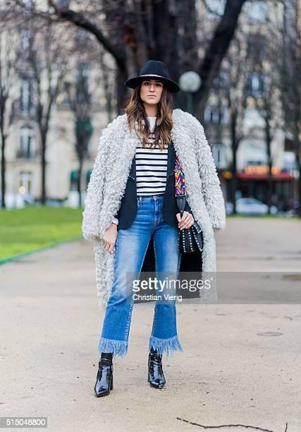 Soraya Bakhtiar is wearinga creme fur coat a hat a striped jumper black Topshop boots a Paul and Joe jacket a MSGM blue denim jeans and a black...