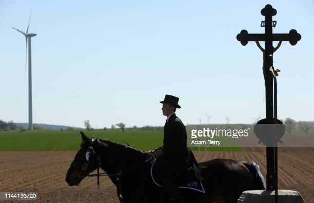 Sorb Easter horseman passes a wind turbine and a crucifix during an annual procession on April 21 2019 in Siebitz Germany Sorbs a Slavic minority in...