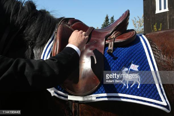 Sorb horseman adjusts his horse's saddle during a break in an annual procession on April 21 2019 in Siebitz Germany Sorbs a Slavic minority in...