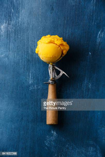 sorbet mango ice cream ball in scoop on blue background - sorbet stock pictures, royalty-free photos & images