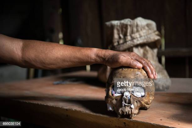 a sorcerer in siquijor island places his hand on a human skull which he uses to cast spells on people. - mago imagens e fotografias de stock