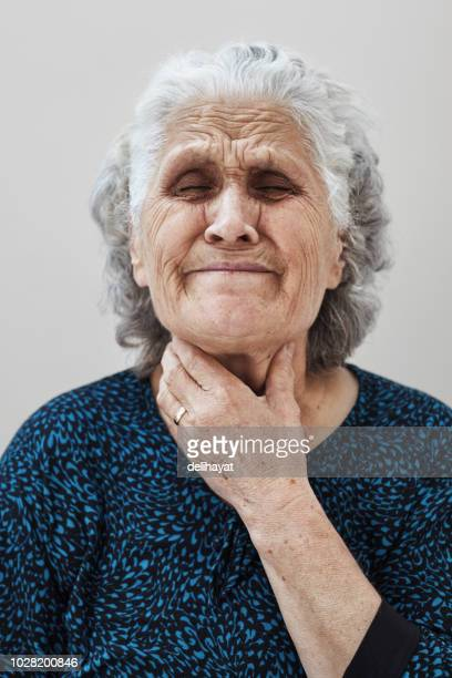 Sore throat, senior woman with neck pain holds her throat