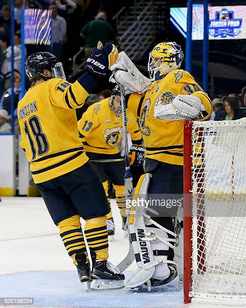 Soren Jonzzon of the Quinnipiac Bobcats consoles Michael Garteig after the loss to the North Dakota Fighting Hawks during the championship game of...