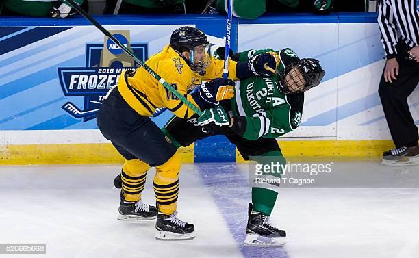 Soren Jonzzon of the Quinnipiac University Bobcats checks Troy Stecher of North Dakota Fighting Hawks during the 2016 NCAA Division I Men's Hockey...