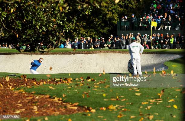 Soren Kjeldsen of Denmark plays his third shot from a bunker on the first hole as caddie Alistair Matheson looks on during the first round of the...