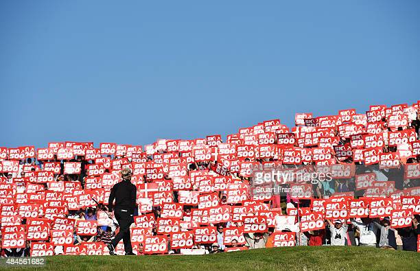 Soren Kjeldsen of Denmark walks onto the 16th green as fans hold placards to celebrate the 500th tournement during the first round of the Made in...