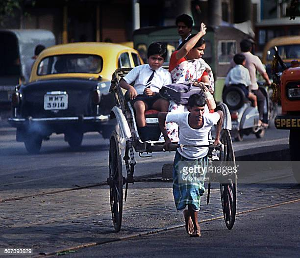 SOrickshawtraffic1217AS––CALCUTTA INDIA––A rickshaw wallah as they are called in India pulls a mother and son to school barefoot through a bustling...