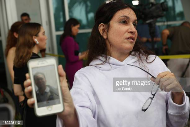 Soriya Cohen shows a picture of her husband, Brad Cohen, who she said is missing after the partial collapse of the 12-story condo tower that he was...